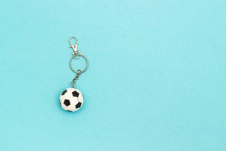 Porte-clés avec ballon de football ou de football sur fond bleu dans un style minimal. Vue de dessus Espace de copie Modèle pour le texte ou votre conception.