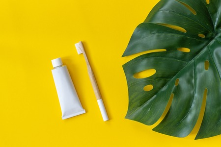 Natural eco-friendly bamboo brush, tube of toothpaste and tropical leaf monstera. Set for washing on paper yellow background. Top view Flat lay. 免版税图像