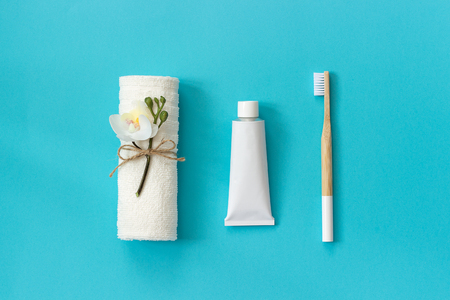 Natural eco-friendly bamboo brush with white bristles, white towel and tube of toothpaste. Set for washing on paper blue background. Copy space for text or your design Top view Flat lay.