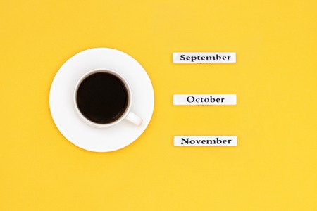 Wooden calendar autumn months September October November and Cup of black coffee aimed at November on yellow background. Concept Top view Flat Lay Copy space