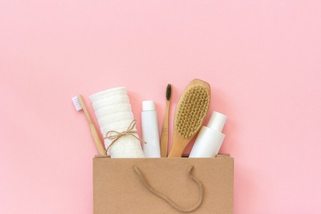 Set of eco cosmetics products and tools for shower or bath Bamboo toothbrush, natural brush, white bottles, towel accessories for body, face and teeth care in paper bag on pink background Copy space