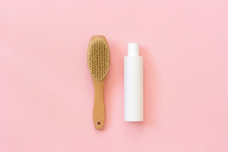 Natural eco brush and white bottle of cream for massage, peeling and body care. Concept of beautiful, healthy body and fight against cellulite. Template Copy space Top view.