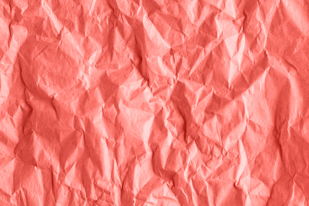 Texture of crumpled rough wrapping paper in coral toned, abstract background.