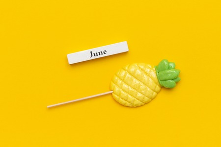 Wooden calendar summer month June and pineapple lollipop on stick on yellow background. Concept vacation, holidays or Hello June. Creative Top view Template.