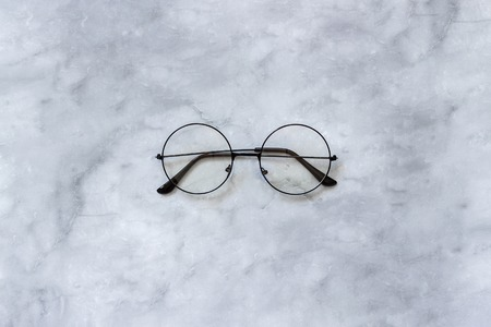 Stylish black round eyeglasses spectacles on marble background. Top view Copy space Minimal style.