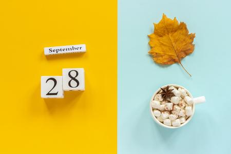 Composition d'automne. Calendrier en bois 28 septembre, tasse de cacao avec des guimauves et des feuilles d'automne jaunes sur fond bleu jaune. Vue de dessus Concept de maquette à plat Bonjour septembre.