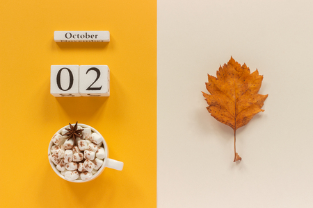 Autumn composition. Wooden calendar October 2, cup of cocoa with marshmallows and yellow autumn leaves on yellow beige background. Top view Flat lay Mockup Concept Hello September. Фото со стока