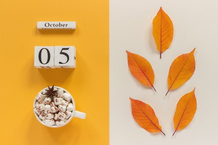 Autumn composition. Wooden calendar October 5, cup of cocoa with marshmallows and yellow autumn leaves on yellow beige background. Top view Flat lay Mockup Concept Hello September.
