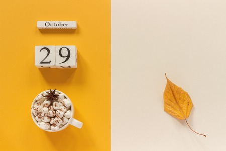 Autumn composition. Wooden calendar October 29, cup of cocoa with marshmallows and yellow autumn leaves on yellow beige background. Top view Flat lay Mockup Concept Hello September.