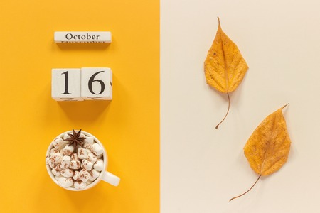 Autumn composition. Wooden calendar October 16, cup of cocoa with marshmallows and yellow autumn leaves on yellow beige background. Top view Flat lay Mockup Concept Hello September.