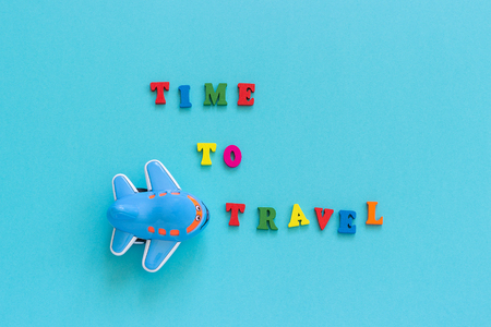 Colorful text Time to travel and children's funny toy plane on blue paper background. Copy space Top view Concept tourism, Template for postcard, greeting card.