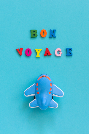 Bon voyage colorful text and children's funny toy plane on blue paper background. Top view Concept tourism, travel. Template for postcard, greeting card. Reklamní fotografie