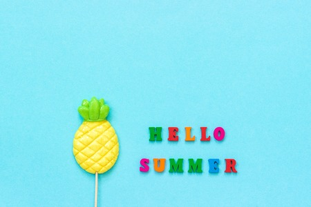 Hello summer text from colorful letters, pineapple lollipop on stick on blue paper background. Concept vacation or holidays Creative Top view Copy space Template Greeting card, postcard.