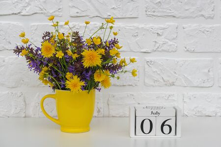 Wooden cubes calendar July 6 and yellow cup with bright colored flowers against white brick wall. Template calendar date for your design Copy space.