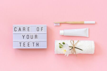 Care of your teeth text on light box and natural eco-friendly bamboo brush for teeth, towel, toothpaste tube. Set for washing on pink background. Concept dental health care Top view.