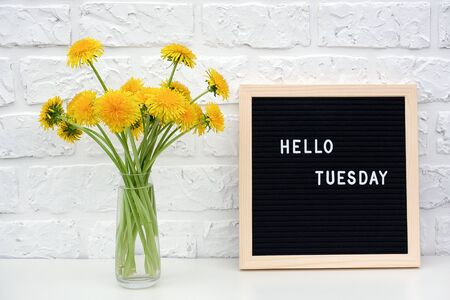 Hello Tuesday words on black letter board and bouquet of yellow dandelions flowers on table against white brick wall. Concept Happy Monday. Template for postcard.