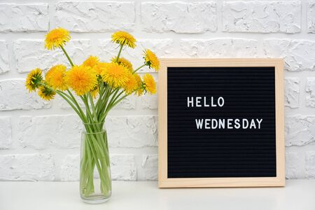Hello Wednesday words on black letter board and bouquet of yellow dandelions flowers on table against white brick wall. Concept Happy Monday. Template for postcard.