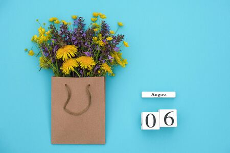 Wooden cubes calendar August 6 and field colorful rustic flowers in craft package on blue background. Greeting card Flat Lay Concept Hello August Template with copy space for text and design. Banco de Imagens