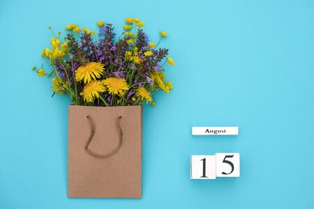 Wooden cubes calendar August 15 and field colorful rustic flowers in craft package on blue background. Greeting card Flat Lay Concept Hello August Template with copy space for text and design.