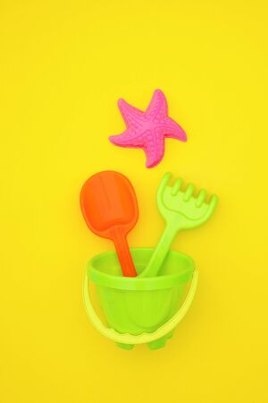 Multicolored set children's toys for summer games in sandbox or on sandy beach on yellow background. Top view Flat lay Concept. Template for your text or design. Zdjęcie Seryjne