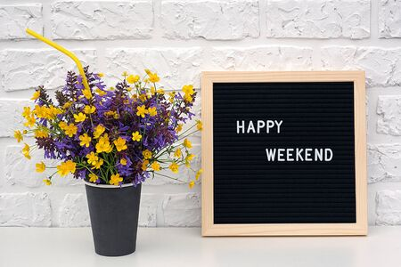 Happy weekend words on black letter board and bouquet of colored flowers in black paper coffee cup with cocktail straw on table against white brick wall. Concept Happy Weekend. Template for postcard.