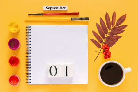 Wooden calendar September 1, cup of coffee, open notepad, autumn colored leaves and watercolor paints on yellow background. Top view Flat lay Mock up Concept Hello September or Back to school.