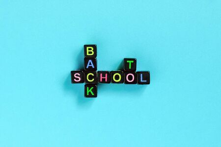 Back to school text from colorful letters on black cubes laid out in form of crossword puzzle, blue background. Concept education and beginning of schoolyear Copy space Top view Flat lay Layout .