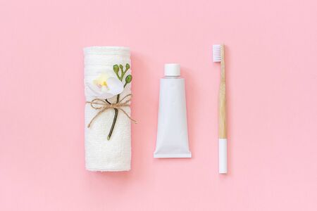 Natural eco-friendly bamboo brush, white towel and tube of toothpaste. Set for washing and brushing your teeth on pink background. Template for design Top view Flat lay.