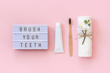Brush your teeth - Light box text and natural eco-friendly bamboo brush for teeth, towel, toothpaste tube. Set for washing on pink background. Concept dental health care Top view Flat lay.