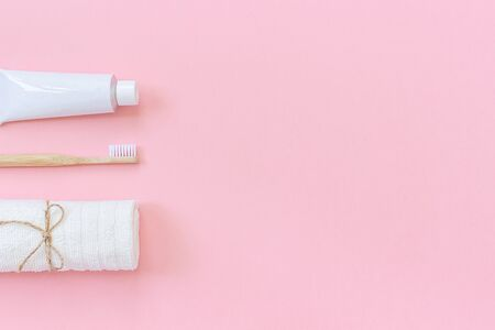 Natural eco-friendly bamboo brush, white towel and tube of toothpaste. Set for washing and brushing your teeth on pink background. Template for design Top view Flat lay Copy space.