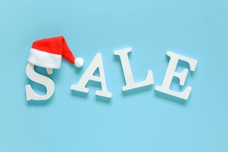 Text SALE from white letters and Santa Claus hat on blue background. Top view Flat lay Copy space Concept New Year or Xmas discount. Creative template for your text, design, ad or advertisement. Stock Photo