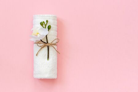 White towel roll tied with rope with sprig of orchid flower on pink paper background. Copy space Template for lettering text or your design. 스톡 콘텐츠