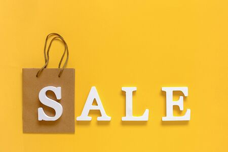 Text SALE from white volume letters and blank shopping bag on yellow background. Top view Flat lay Copy space Concept discount. Creative template for your text, design, ad or advertisement. Foto de archivo - 129909739