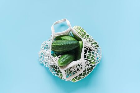 Fresh green cucumbers vegetables in reusable shopping eco-frendly mesh bag on blue background. Concept no plastic and zero waste. Copy space Top view Flat lay. Foto de archivo - 129909750