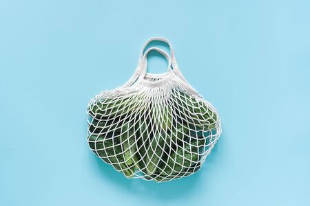 Fresh green cucumbers vegetables in reusable shopping eco-frendly mesh bag on blue background. Concept no plastic and zero waste. Copy space Top view Flat lay. 版權商用圖片 - 129909763