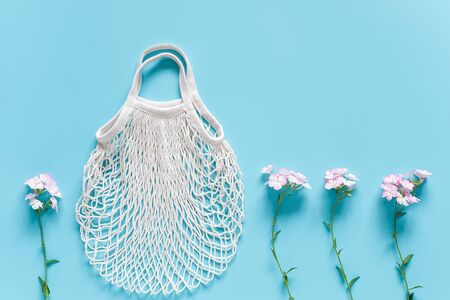 Delicate flowers and white reusable shopping eco mesh bag on blue background. Concept no plastic, zero waste and caring for environment. Copy space Top view Layout for your design. Stockfoto