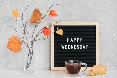 Happy Wednesday text on black letter board and bouquet of branches with yellow leaves on clothespins in vase on table Template for postcard, greeting card Concept Hello autumn Wednesday.