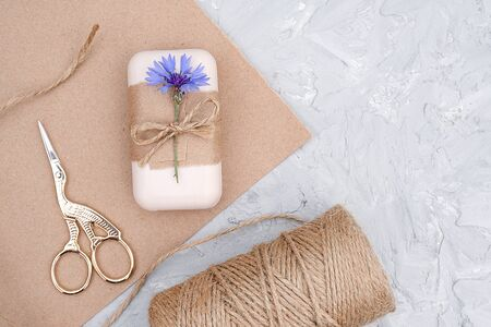 Packaging of natural handmade soap, decorated kraft paper , blue flower, skein of twine and scissors. Concept of organic cosmetics. Top view Flat lay Copy space Template for design. 스톡 콘텐츠