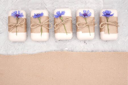 Handmade natural soap set decorated with craft paper, scourge and blue flowers. Organic cosmetics concept. Top view Flat lay Copy space Template for design.
