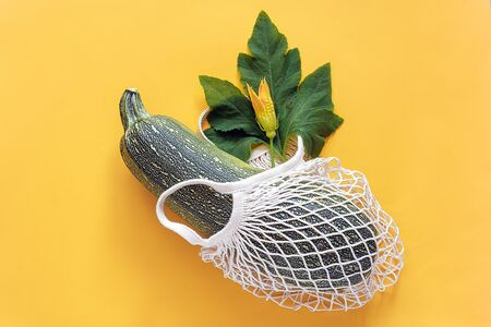 Fresh zucchini with green leaf and flower in reusable shopping eco-friendly mesh bag on yellow background. Concept Organic squash vegetable and no plastic, zero waste. Copy space Top view Flat lay. 版權商用圖片 - 129909849