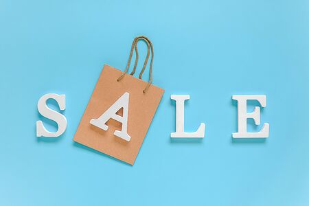 Text SALE from white volume letters and paper shopping bag on blue background. Top view Flat lay Copy space Concept discount. Creative template for your text, design, ad or advertisement. Foto de archivo - 129909869
