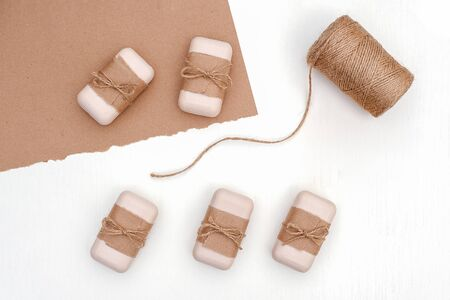 Soap set decorated with craft paper and skein of twine on white background. Organic cosmetics concept. Top view Flat lay Template for design.
