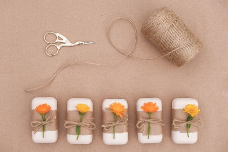 Handmade natural soap set decorated with craft paper, orange calendula flowers, skein of twine and scissors . Organic cosmetics concept. Top view Flat lay Template for design.
