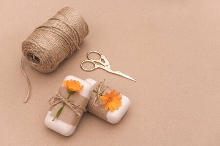 Handmade natural soap decorated with craft paper, orange calendula flowers, skein of twine and scissors . Organic cosmetics concept. Copy space for text Template for yuor design.