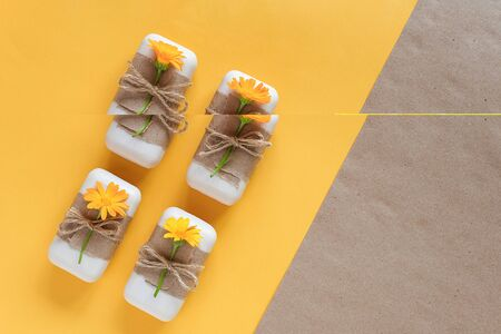Handmade natural soap set decorated with craft paper, scourge and orange calendula flowers. Organic cosmetics concept. Top view Flat lay Template for design.