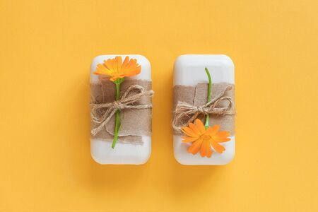 Handmade natural soap set decorated with craft paper, scourge and orange calendula flowers on yellow background. Organic cosmetics concept. Top view Flat lay Template for design. 스톡 콘텐츠