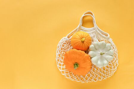 Fresh harvest vegetables gourds pumpkin, pattypan squash on shopping eco-friendly mesh bag on yellow background. Concept Organic vegetable harvest. Top view Flat lay Copy space Template. 版權商用圖片