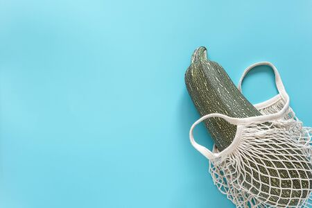 Fresh zucchini in reusable shopping eco-friendly mesh bag on blue background. Concept Organic squash vegetable and no plastic, zero waste. Copy space Top view Flat lay.