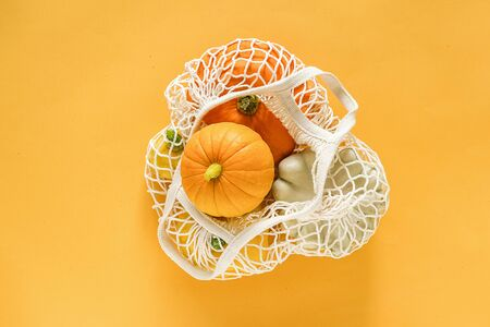Fresh harvest vegetables gourds pumpkin, pattypan squash in shopping eco-friendly mesh bag on yellow background. Concept Organic vegetable harvest. Top view Flat lay Copy space Template. 版權商用圖片 - 129909913