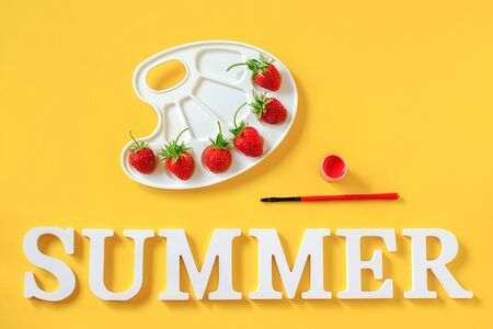 Text Summer, red ripe strawberries on an artistic palette, brush and gouache on yellow background Copy space. Creative concept summer colors paint. Top view Flat lay Template for postcard invitation